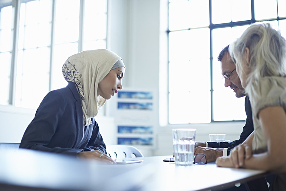 A woman wearing a hijab and sitting at a table is talking to an older man and an older woman